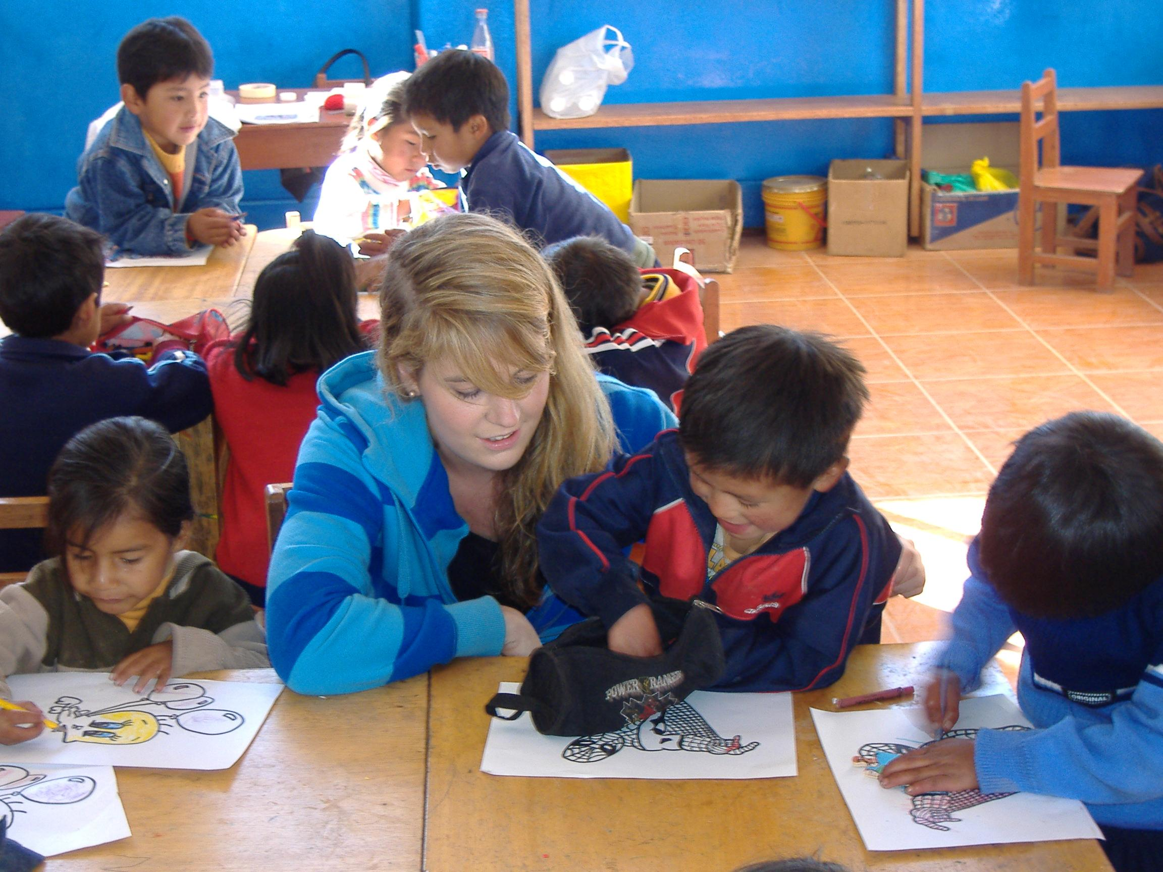 Projects Abroad Childcare volunteer helps children in Peru draw within a care centre placement.